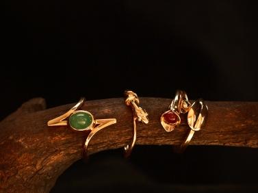 Ringar i guld, smaragd o röd bärnsten